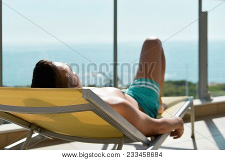 closeup of a young caucasian man in swimsuit lying down face up on a sunlounger in a terrace