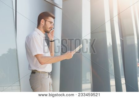 Attractive Businessman Or Lawyer In Eyeglasses Holding Digital Tablet And Talking On Mobile Phone Wh