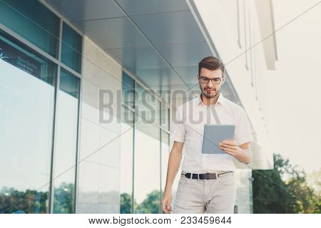 Attractive Concentrated Businessman Or Lawyer In Eyeglasses Is Reading On Digital Tablet While Stand