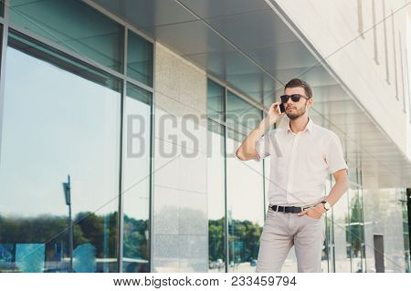 Attractive Pensive Businessman Or Lawyer In Sunglasses Is Talking On Cell Phone And Putting His Hand