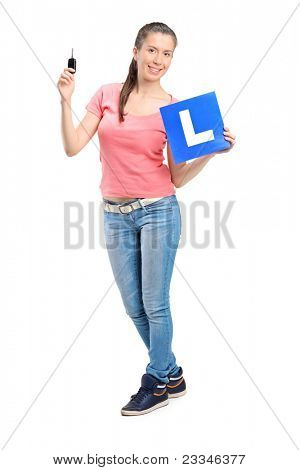 Happy teenager holding a car key and L plate isolated against white background