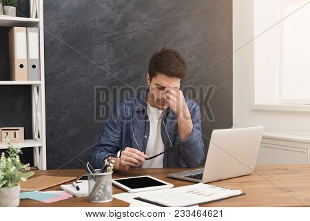 Eyes Pain. Tired, Overworked Businessman With Laptop In Modern Office Interior. Handsome Man At Work