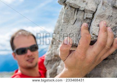 Closeup Of Climber's Hand Gripping A Rock.