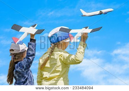 Two Girls Kid Playing With Toy Airplane And A Real Passenger Plane Taking Off In The Sky, Against Bl