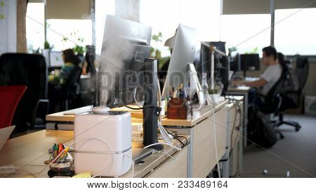 Working Humidifier On The Background Of Young People Working In The Office. Healthy Working Environm