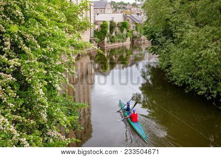 Two women kayaking down the River Avon (Bristol Avon) along scenic Bradford-on-Avon, a town and civil parish in West Wiltshire, Southwest England, UK