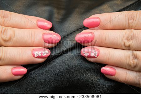 The Nails Are Covered With Pink Gel Polish With A White Sticker With A Picture Of A Flower, Located
