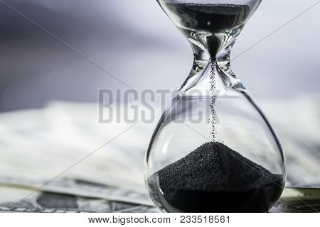 Closed Up Of Sand Falling In Sandglass Or Hourglass On Us Dollar Bills As Time Running, Long Term In
