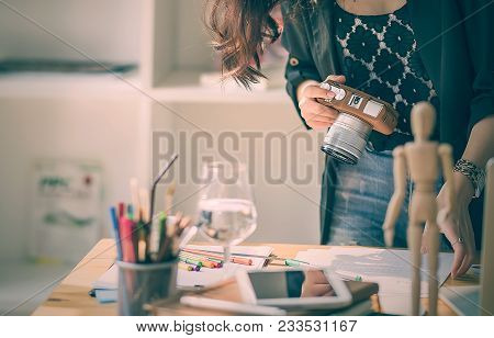 Cropped Image Of Young Designer Woman Working With Paperwork And Holding Digital Camera While Standi