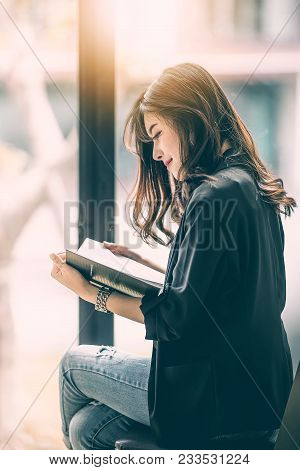 Beautiful Woman Reading A Book By The Window With Morning Sunlight