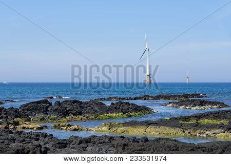 Landscape Of Coast With Wind Generator In Gujwa-eup, Jeju, Korea. Jeju Island Is Famous For Beautifu