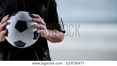 Digital composite of soccer player with ball in the hands, blue, white and brown blurred background