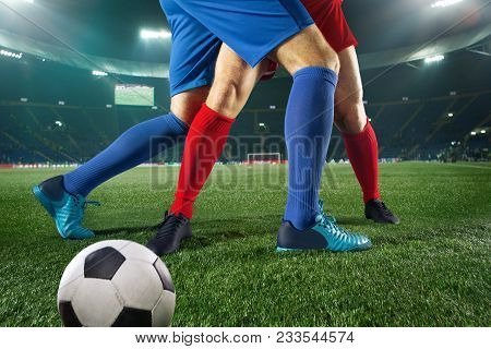 Football Players Tackling For The Ball Over Green Grass At Stadium. Professional Football Soccer Pla