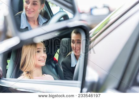 Student in driving school at the wheel of a car with her instructor learning to drive