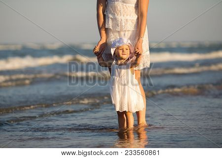 Young Happy Family Walking Along The Seashore At The Day Time. Mother Holding Her Daughter By The Ha