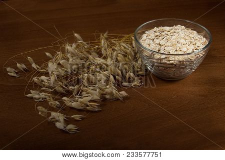Oat Ears Stems And Oat Flakes In A Bowl On Dark Brown Wood Background. Oatmeal Flakes Coarse. Large-