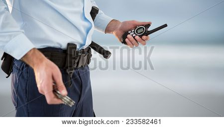 Digital composite of security guard with walkie-talkie and cuffs. blurred back