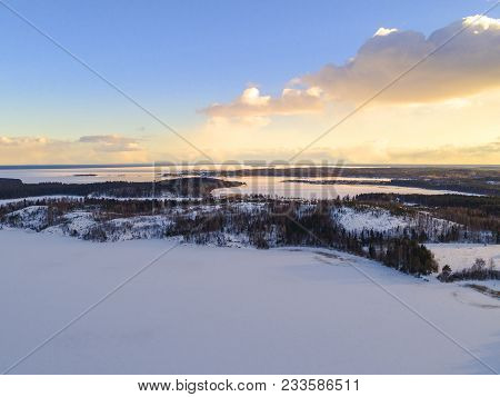 Aerial Drone View Of A Winter Landscape. Snow Covered Forest And Lakes From The Top. Sunrise In  Nat