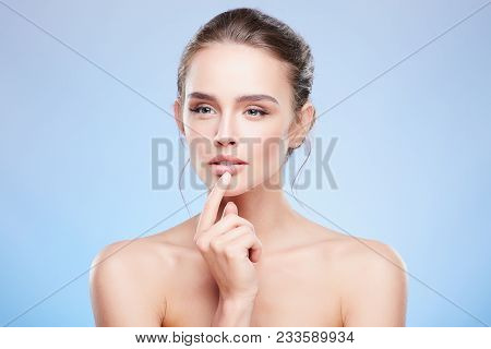 Woman Touching Lower Lip And Looking Suspiciously