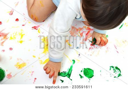 The Little Girl Is Stained With Multicolored Paints. Little Baby Paint On Hands. Painted Children's