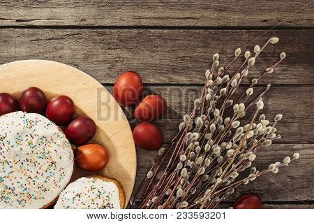 Top View Of Painted Chicken Eggs, Easter Cakes And Catkins On Wooden Surface