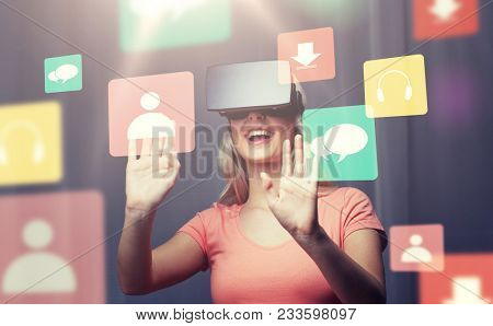 technology, virtual reality, entertainment and people concept - happy young woman with virtual reality headset or 3d glasses playing game at home looking at menu icons projection