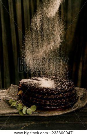 Close Up Decorating Chocolate Cake With Sugar Powder. Dark Vintage Stillife
