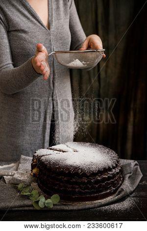 Close Up Woman Decorating Chocolate Cake With Sugar Powder. Dark Vintage Stillife