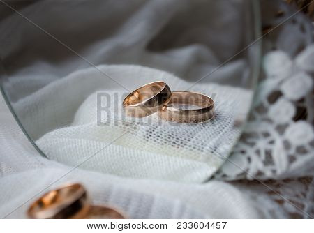 Wedding Rings On White Cloth In The Reflection Of The Mirror
