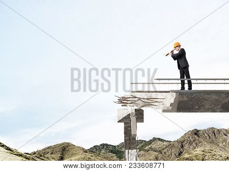 Young Engineer In Suit And Helmet Looking In Spyglass While Standing On Broken Bridge With Skyscape