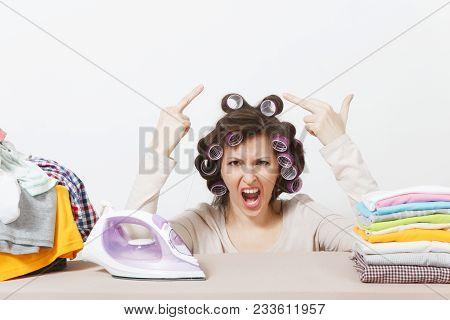 Crazy fun housewife with curlers on hair in light clothes ironing family clothing on ironing board with iron. Woman isolated on white background. Housekeeping concept. Copy space for advertisement poster