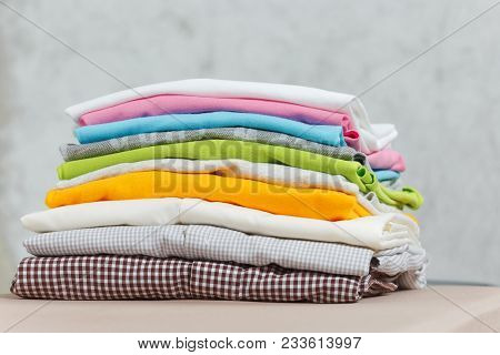 Close Up Pile Of Ironing Colorful Clothes, Washed Laundry, Family Clothing On Ironing Board Isolated