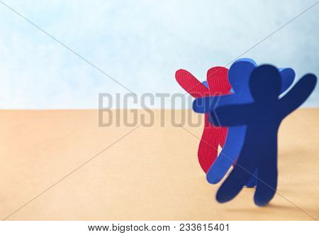 One red paper human among blue ones on table. Difference and uniqueness concept