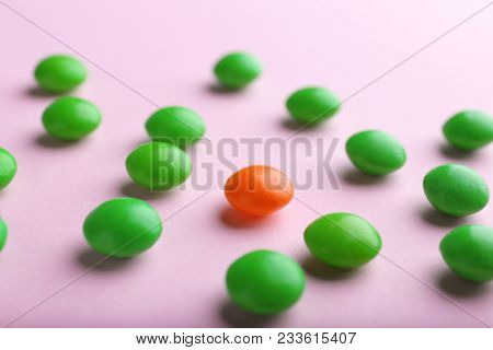 One red drop among green on color background. Difference and uniqueness concept
