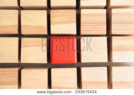 One red cube among wooden ones. Difference and uniqueness concept