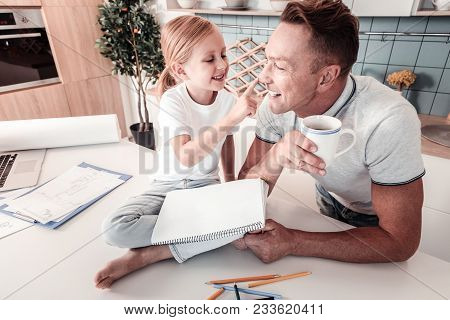 Happy Weekend. Funny Girl Keeping Smile On Her Face And Touching Nose Of Her Daddy While Sitting On