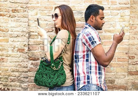 Bored Multiracial Couple Using Mobile Smart Phone - Addiction Isolation Concept With Millennials You