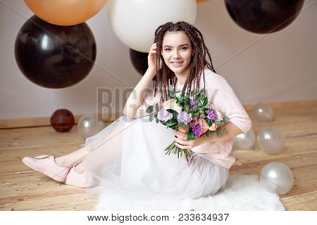 Smiling woman with dreadlocks hairstyle holding a bouquet of flowers in hands indoors. poster