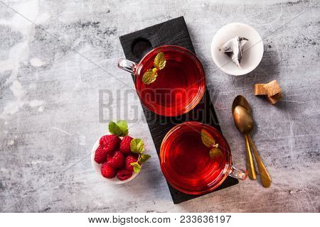 Hot Raspberry Tea In Two Transparent Cups On A Stone Table. Fresh Berries, Cubes Of Cane Sugar And A