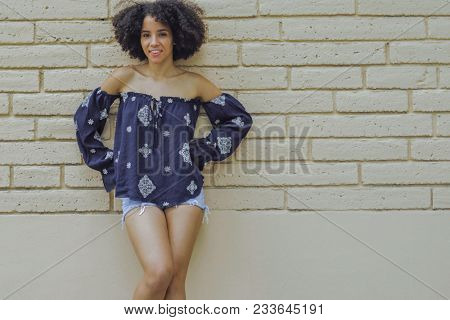 Content coquettish girl with short curls posing in trendy shirt and shorts standing with hands on waist looking at camera.