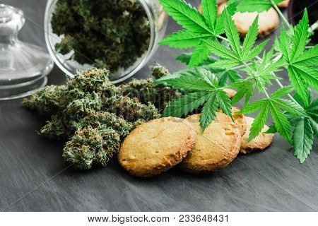 Cookies With Cannabis And Buds Of Marijuana On The Table. A Can Of Cannabis Buds Young Cannabis Plan