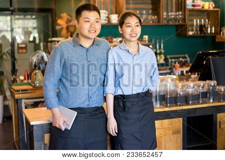 Ambitious Asian Couple Running Own Cafe Together. Cheerful Young Asian Colleagues Meeting Client In