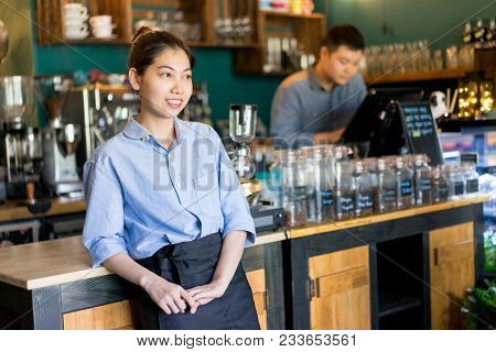 Cheerful Dreamy Asian Waitress Leaning On Bar Counter And Enjoying Her Work. Happy Attractive Young