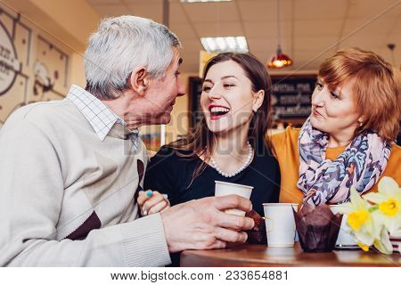 Happy Family Spending Time Together. Senoir Family Couple With Adult Daughter Chat And Laugh In Cafe