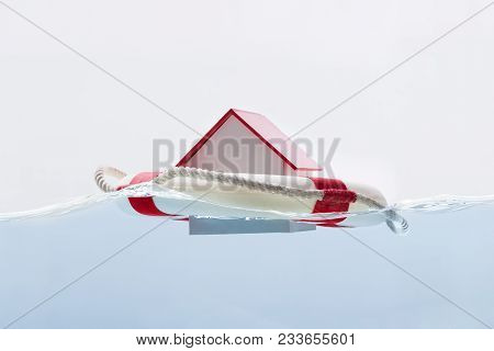 Close-up Of A House Floating On Lifebuoy Against White Background