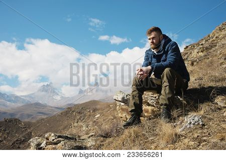 A Portrait Of A Stylish Bearded Hipster Sitting On A Rock Against The Backdrop Of Epic Rocks And Con