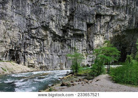 Background Rock And River In Ravine Or Canyon. Mountain River Flows In Canyon On Background Of Rock