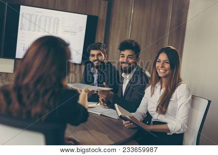 Young Business Woman On A Job Interview Offering Her Resume To A Commission Representative. Focus On