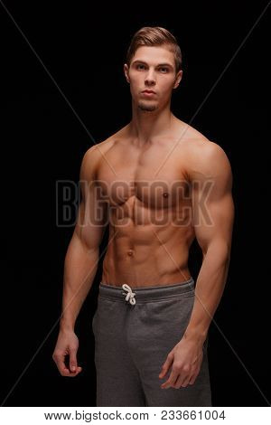 Strong, Muscular Handsome Man Showing Off His Biceps On A Black Background. Gym, Workout, Exercising