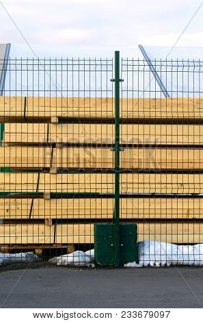 Hewn, Carved Square Logs. Lumber Neatly Stacked Behind The Fence